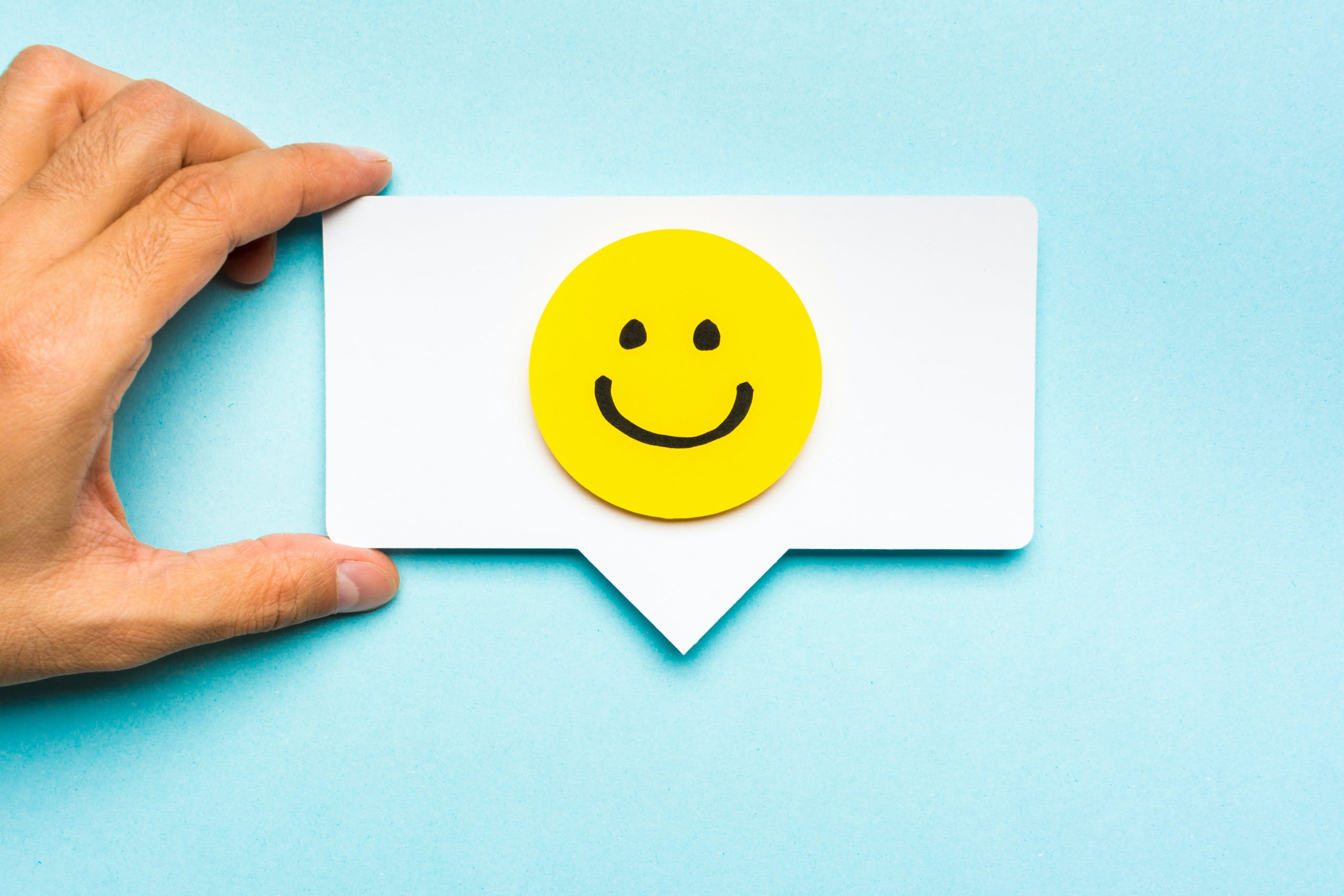 smiley face on speech bubble in hand