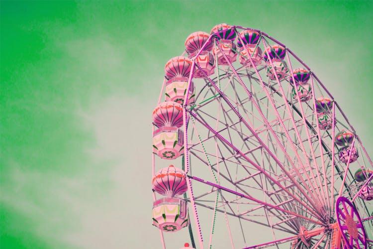 pink tinted ferris wheel against green sky