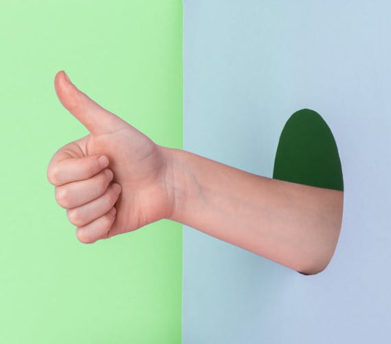 Hand showing a thumb up through a hole in the wall