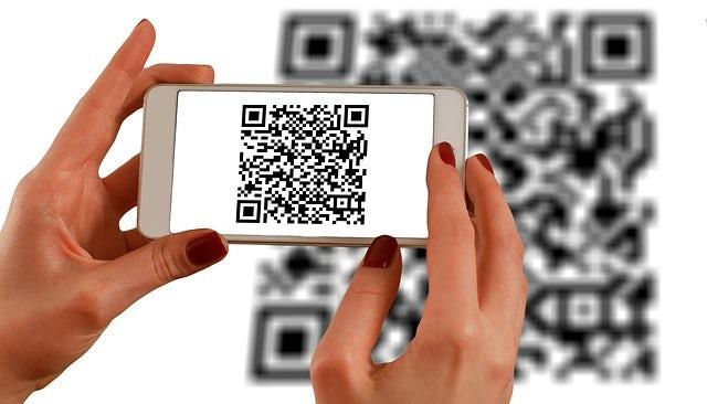 Hands with smartphone scanning QR code