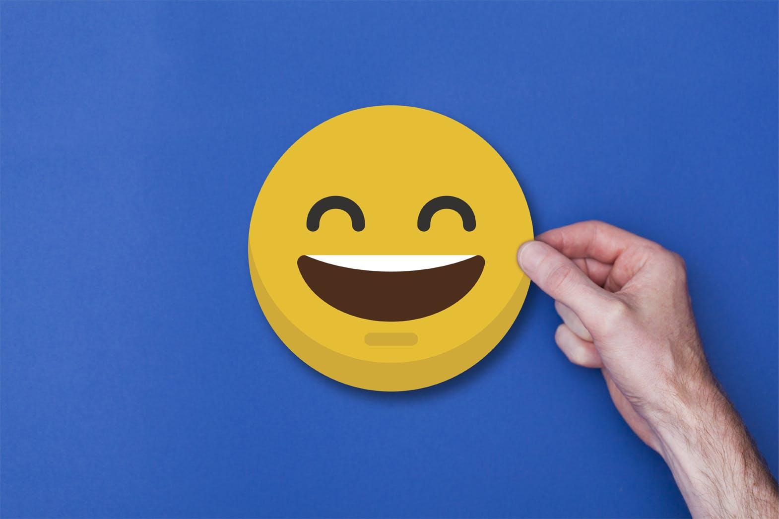 Male hand holding a emoji emoticon smiley head icon