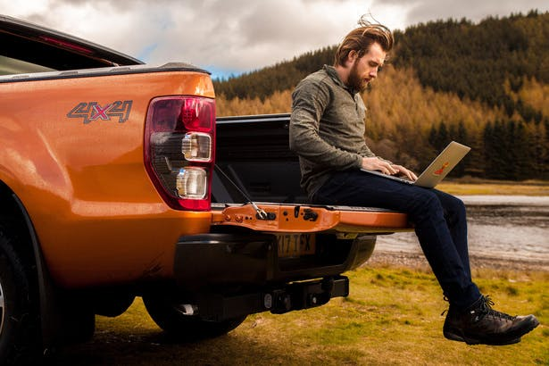 man sitting on back of Jeep with laptop