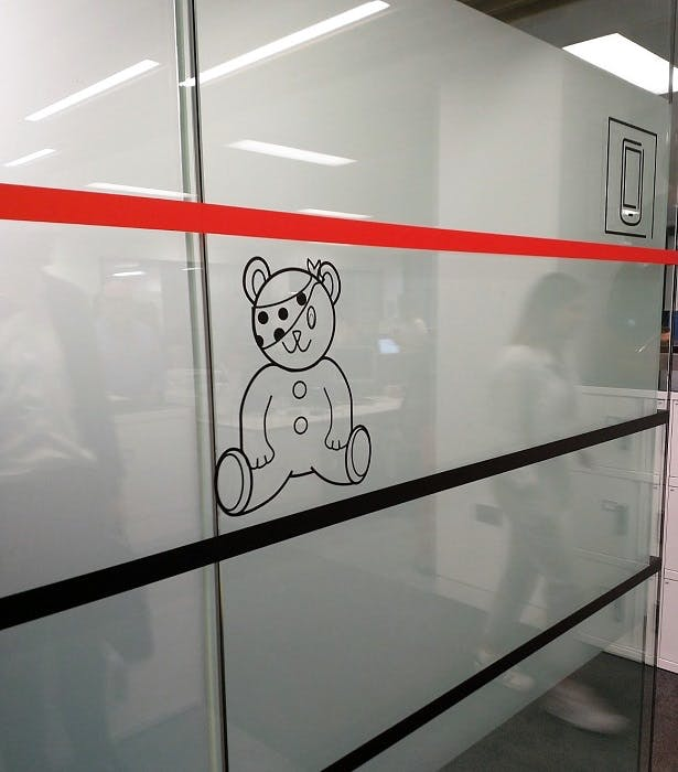 A glass-walled meeting room, with the Children In Need mascot Pudsey Bear adorning the side.