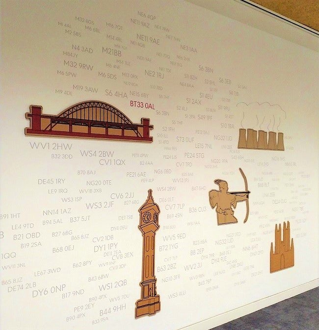 A wall of Post Office branch postcodes, decorated here and there by images of British monuments.