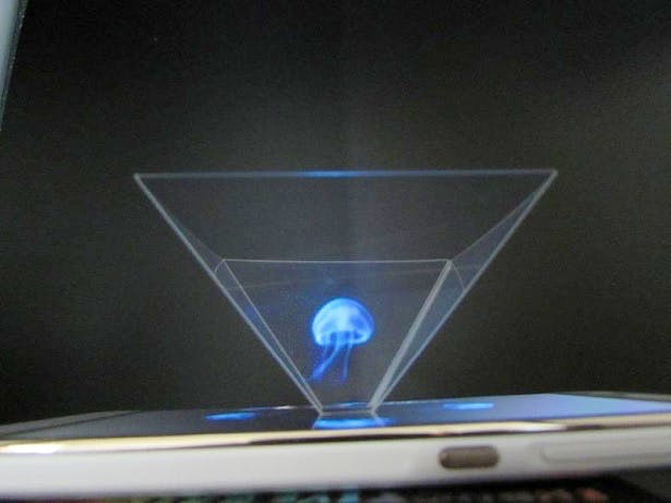 A smartphone on its side, projecting a holographic image of a jellyfish