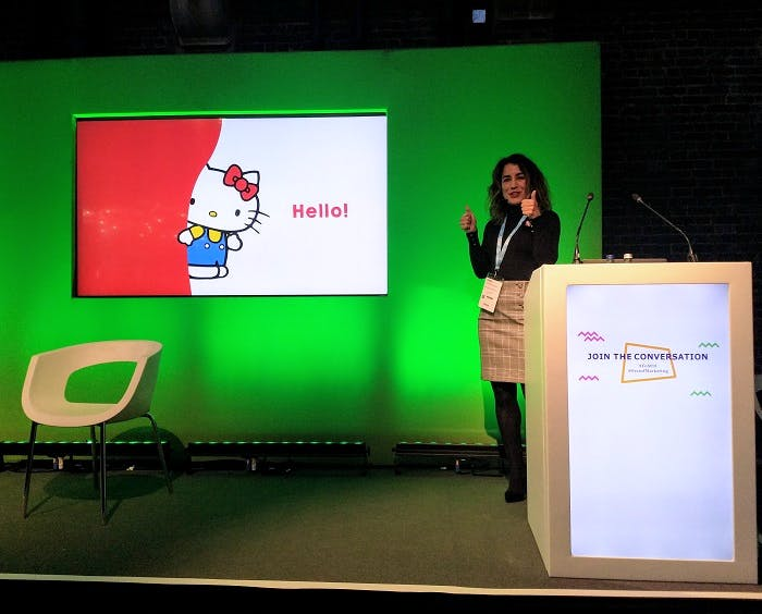 Martina Longueira gives a thumbs up on the Festival of Marketing content stage in front of a picture of Hello Kitty saying hello