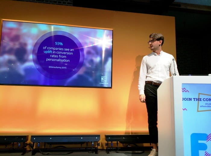 Nick Mottershead stands next to a slide with a statistic reading: 93% of companies see an uplift in conversion rates from personalisation (Econsultancy 2017)