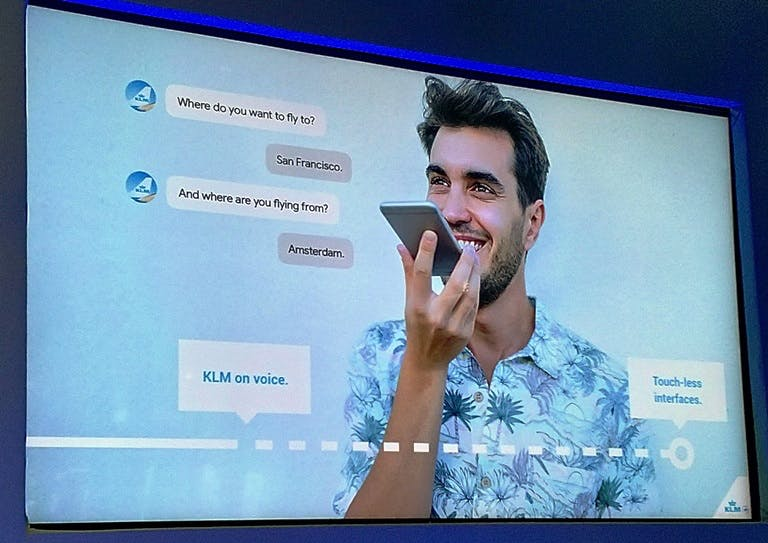 Presentation slide of a man using his mobile to converse with a KLM bot using voice.