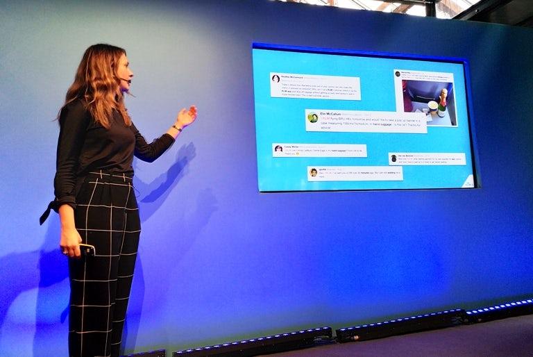 Martine van der Lee stands next to a presentation slide of feedback received on social media by KLM.