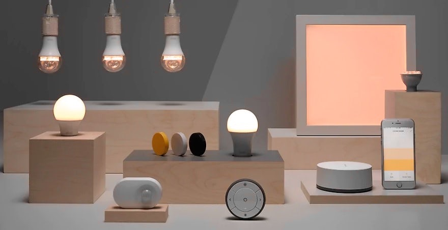 An array of smart lighting products by IKEA, together with a smartphone and devices to control them.