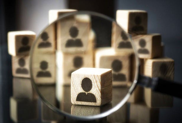 Stock image of wooden blocks depicting customers, with one magnified by a magnifying glass