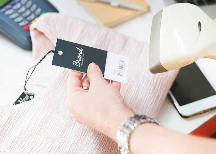 Person scanning clothing label at checkout