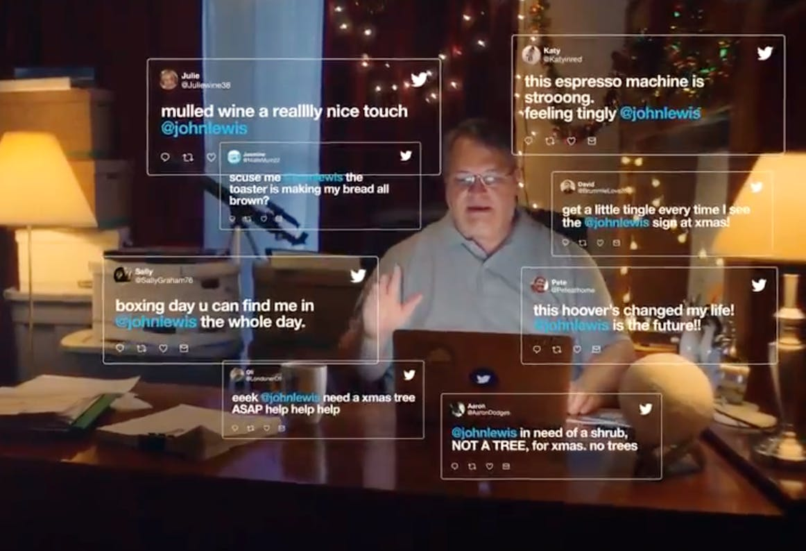 A still from the Twitter John Lewis Christmas ad, showing Mr. Lewis at his desk, with tweets in the air around him.
