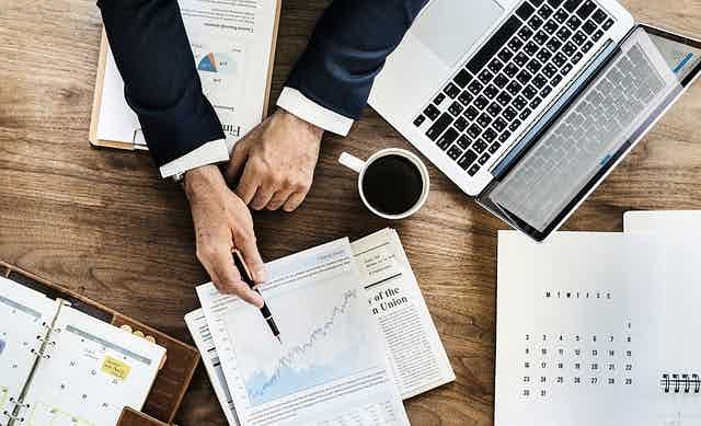 Stock image of paperwork, coffee, laptop