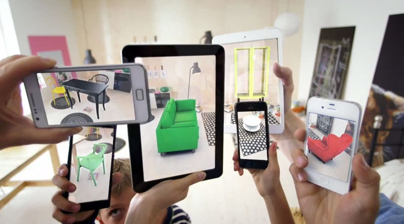 Several hands hold up smartphones, which are projecting different items of furniture into a room via augmented reality.