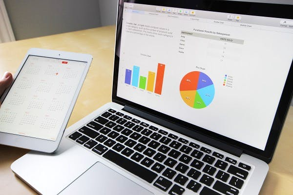 Stock image of laptop showing graphs on screen and next to it, a hand holding a tablet.