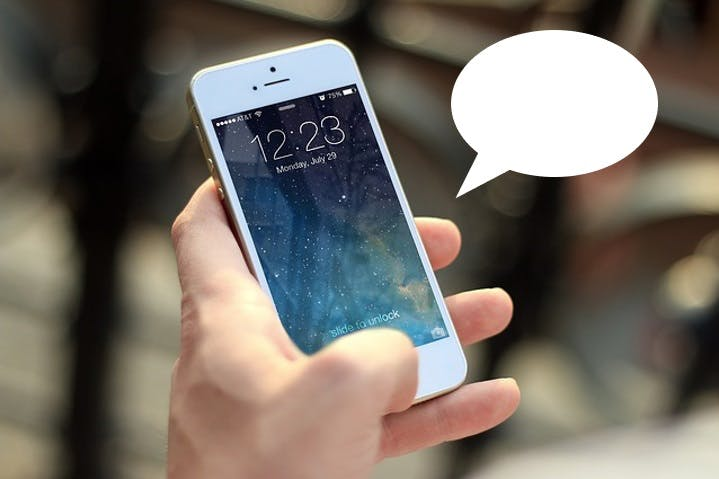 Stock image of a hand holding a mobile phone, with a speech bubble issuing from it.