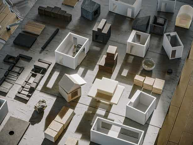 Numerous small housing models laid out on a wooden surface