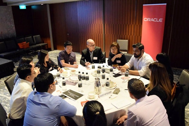 Attendees at Econsultancy's Digital Cream roundtable event discuss agile marketing, with an Oracle banner behind their table.