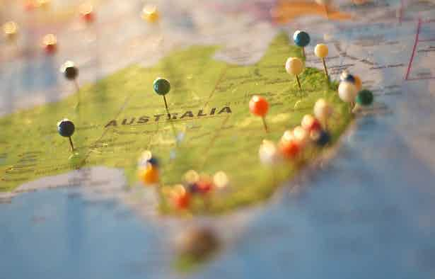 A map of Australia with round-headed colourful pins stuck into it.