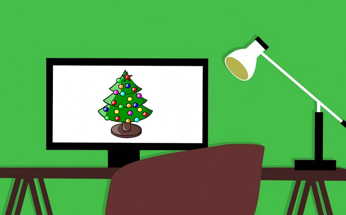 Vector graphic of a desk with an anglepoise lamp and a PC monitor on top. The PC monitor has a Christmas tree displayed on it.