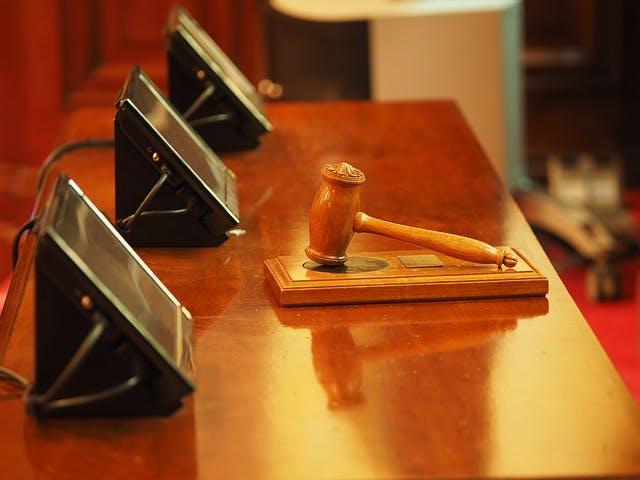 A wooden gavel resting on a table in front of three screens