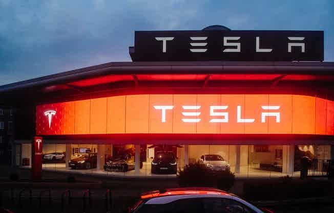 View from the street of Tesla Motors showroom with multiple luxury Tesla cars inside. Tesla is an American company that designs, manufactures, and sells electric cars