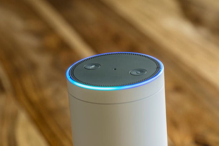 White Amazon Echo Plus activated recognition system photographed on wooden table in living room.