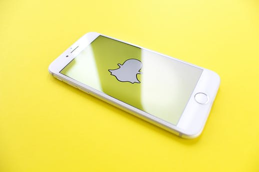 Smartphone displaying Snapchat logo against a yellow background