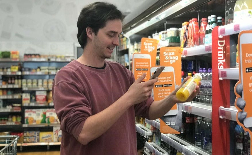 A man scans a bottle of orange juice with his smartphone in Sainsbury's Holborn Circus store.