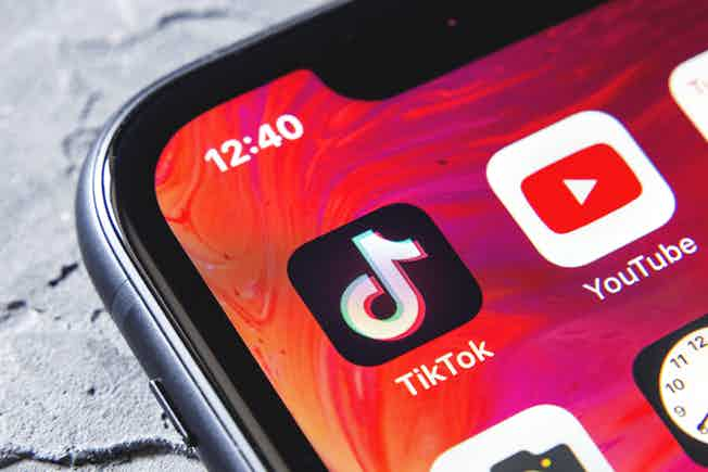 The corner of a smartphone screen showing the TikTok app next to the YouTube app and other icons.