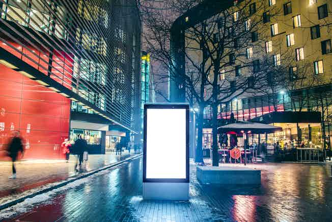 An illuminated blank billboard at night