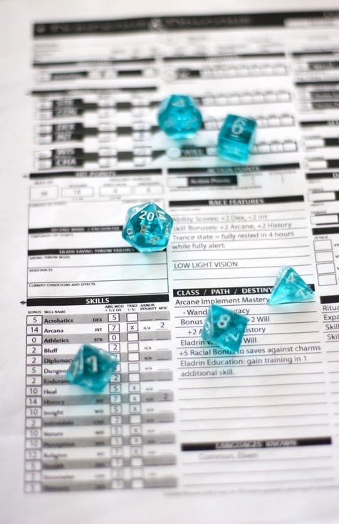 A Dungeons and Dragons character sheet with six translucent turquoise dice on top