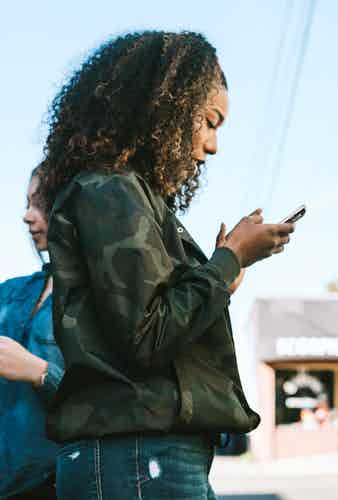woman in camo jacket looking at smartphone exterior