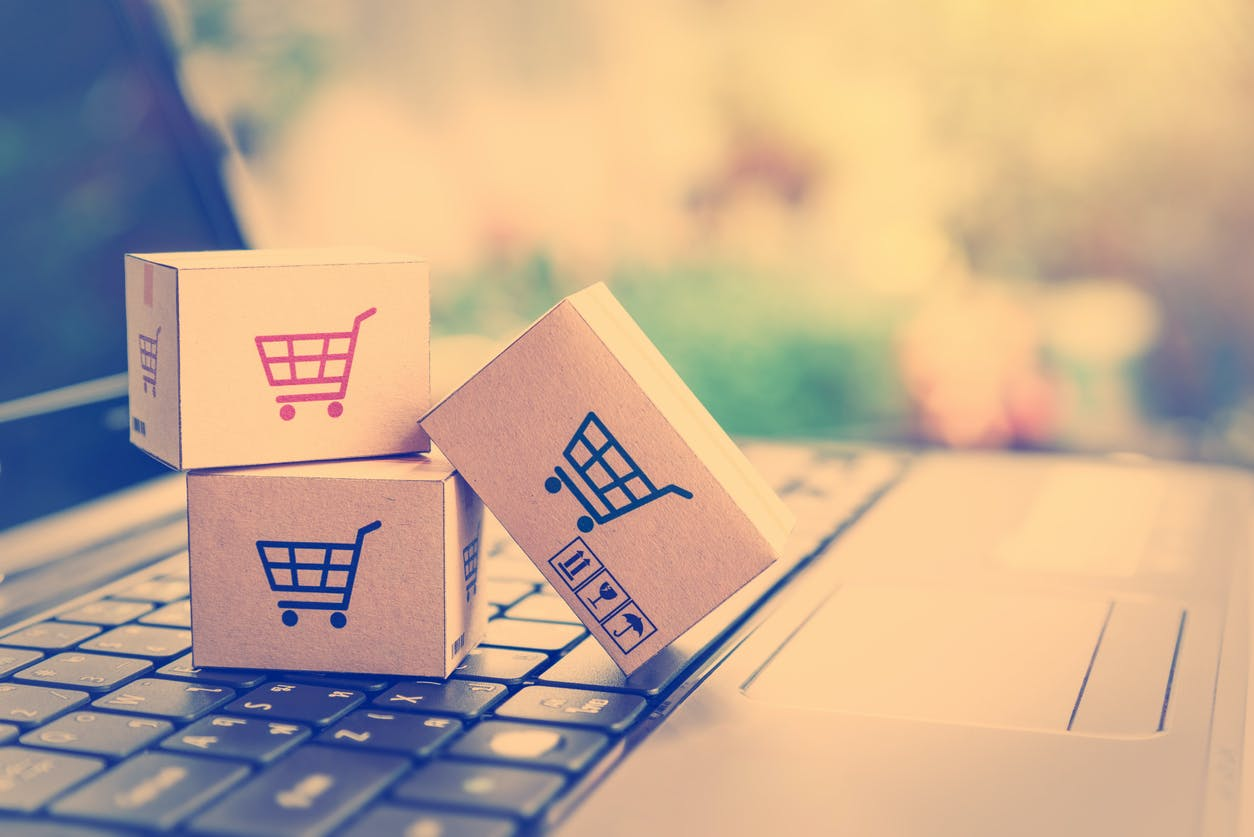 Paper cartons with a shopping cart or trolley logo on a laptop keyboard, depicts customers order things from retailer sites via the internet.