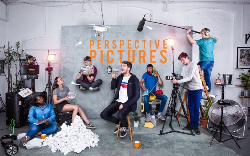 A group of young people striking poses in a studio with the words 'Perspective Pictures' overlaid on the backdrop. Rupert Rixon sits in the middle holding a megaphone.