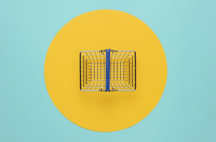 Mini shopping basket on blue background with yellow circle