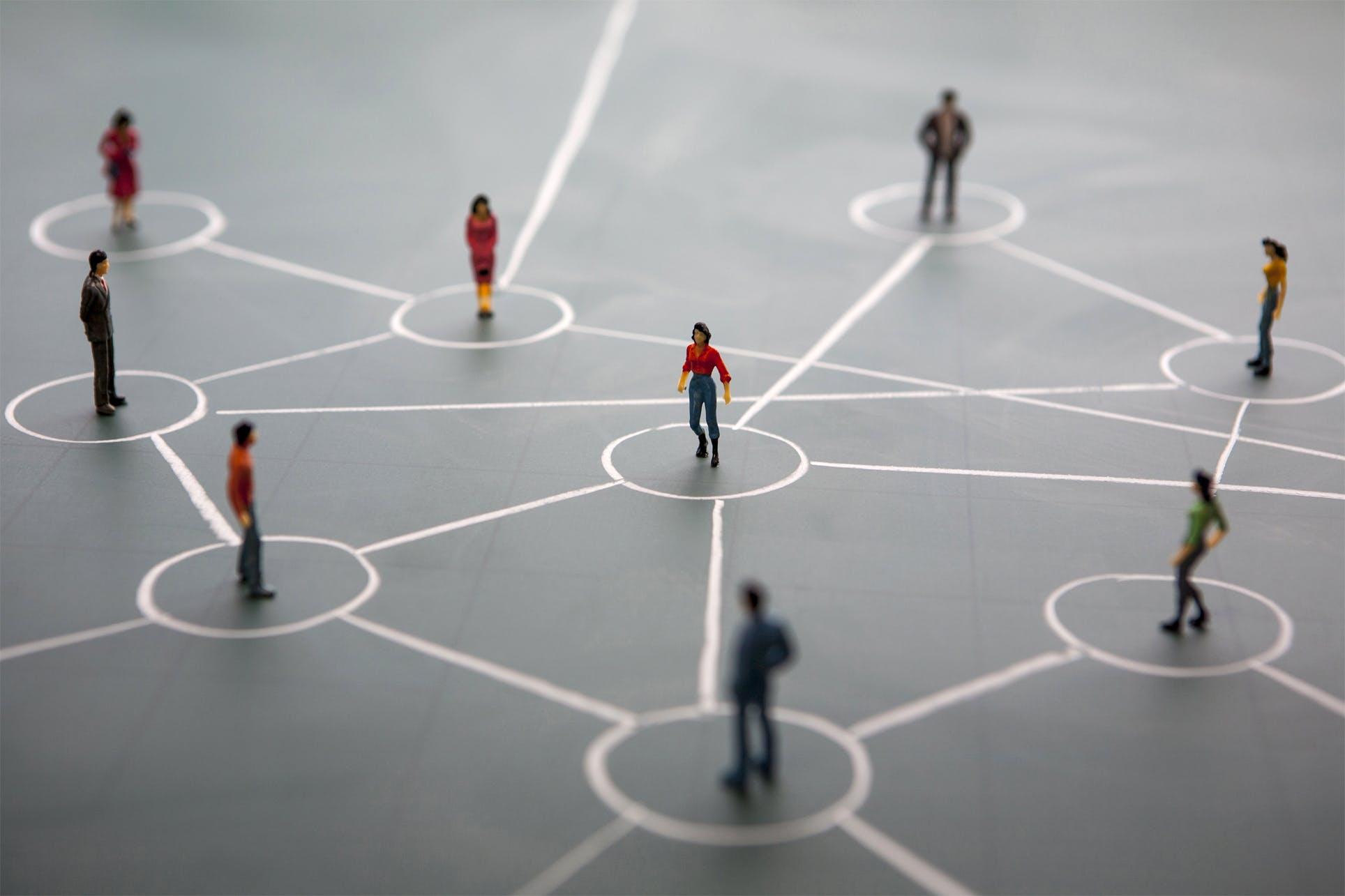 miniature model people standing on drawn chalk network