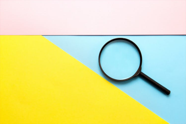 Magnifying glass on blue pink yellow background