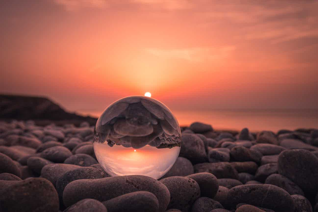 crystal ball on rock beach at sunset