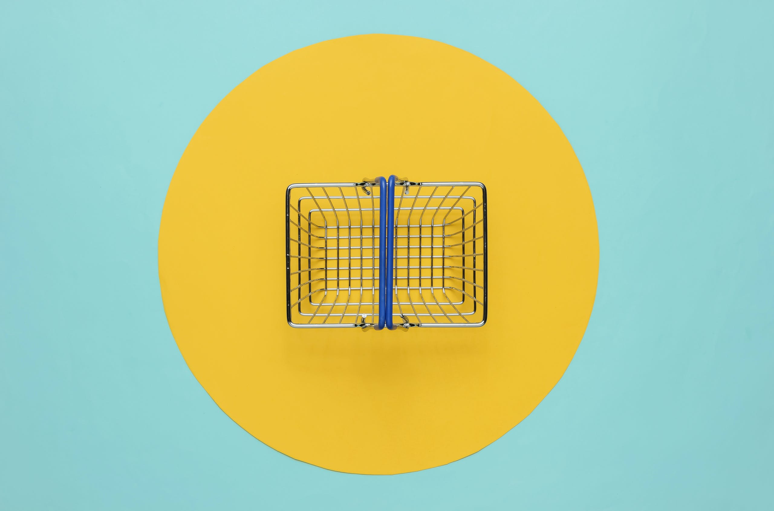 Mini-shopping-basket-on-blue-background-with-yellow-circle-scaled