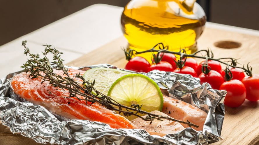 baked salmon in foil with herbs tomatoes and olive oil on the side