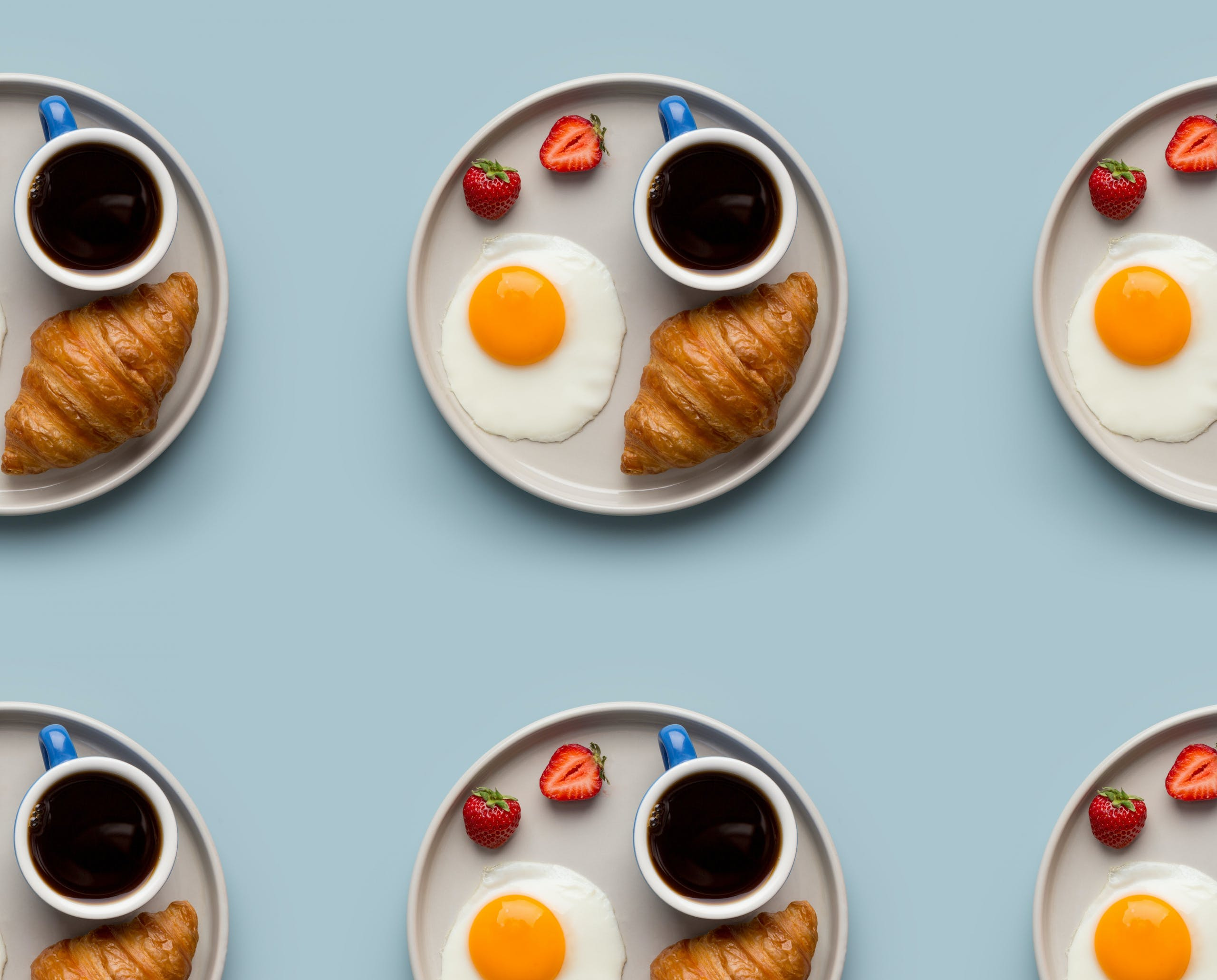 repeated plates of coffee, fried egg, strawberries and croissant in a grid pattern