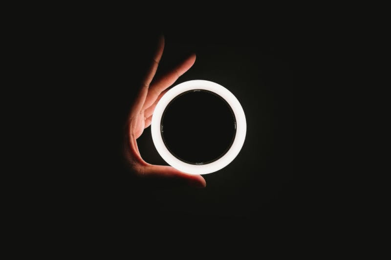hand grasping glowing white ring on black background