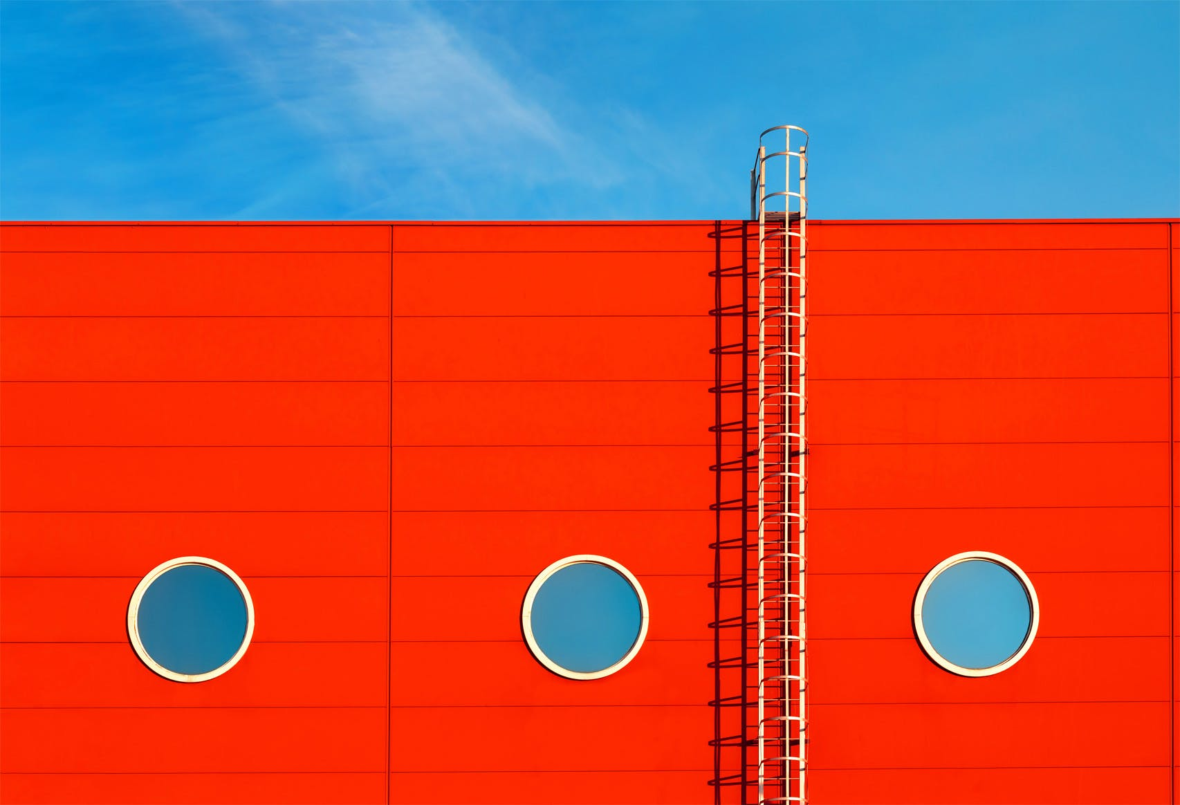 white ladder on red background-with port holes on blue sky