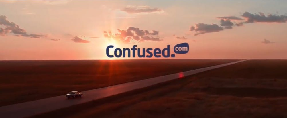 A screencap from the Confused.com 'From Confusion to Clarity' ad spot showing a car driving into the sunset with the Confused.com logo above.