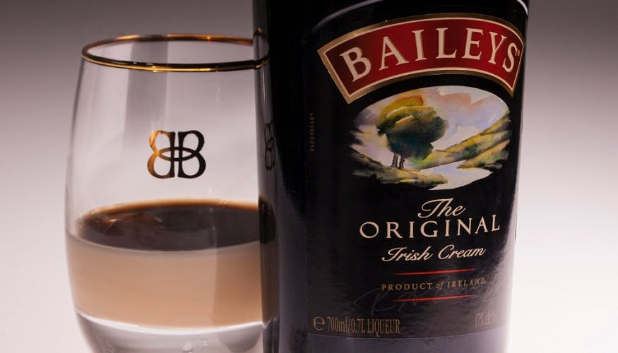 Close-up photograph of a bottle of Baileys alongside a glass that has a small amount poured into it.
