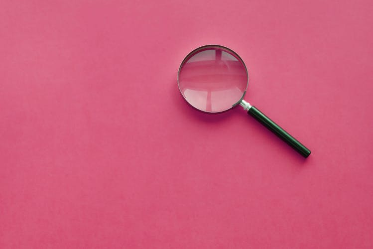 magnifying glass on deep pink background