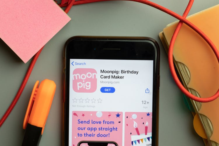 A phone screen displaying the Moonpig app with a marker pen and a binder arranged around it.
