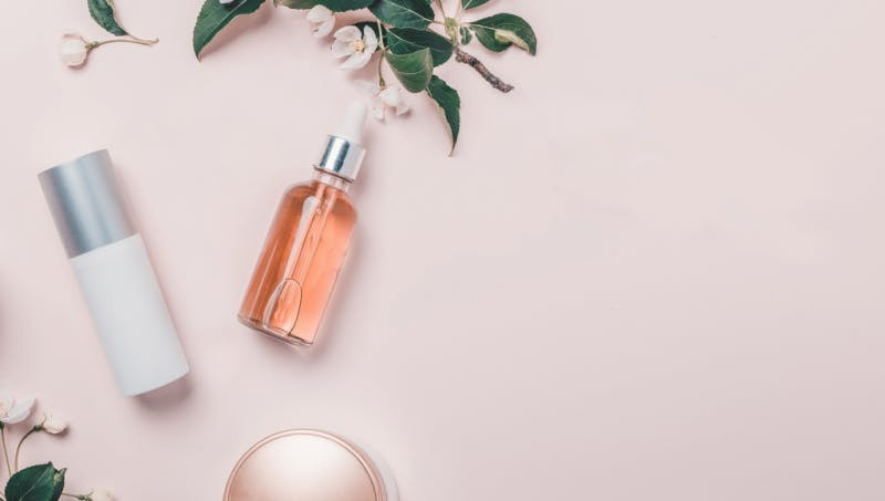 lancome bottles and plant on powder pink background